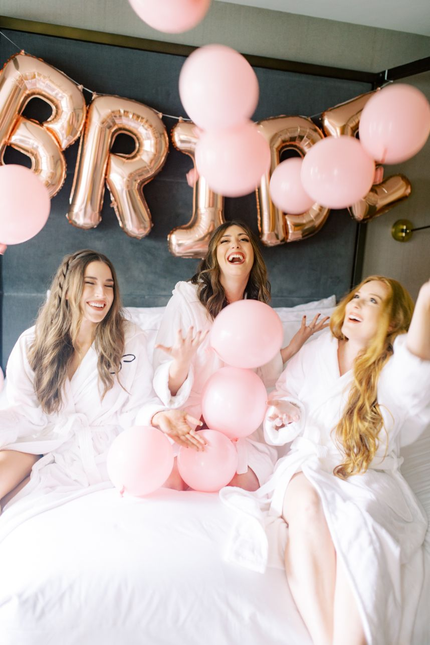 girls on a hotel bed with balloons - each enneagram type as a bride