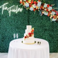 wedding cake with colorful florals, wedding greenery wall, neon wedding sign